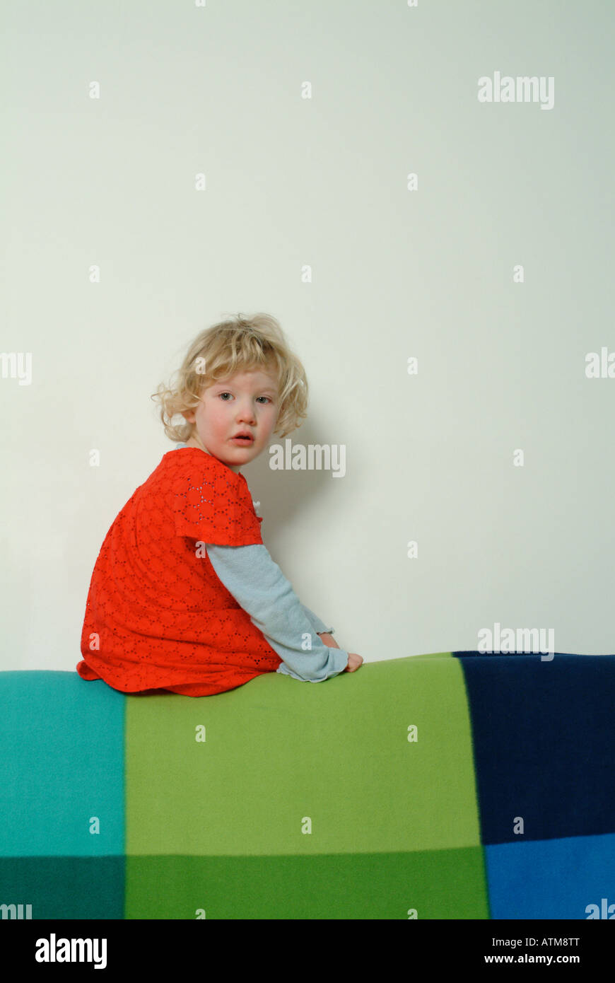 Little girl in red dress sitting on the back of a sofa - Stock Image