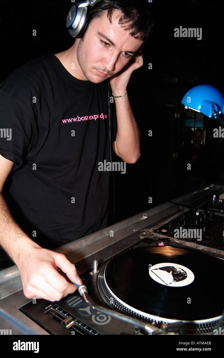 Club DJ Behind the Decks in a Nightclub - Stock Image
