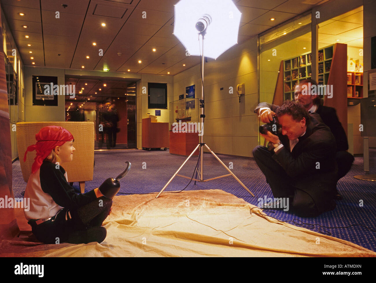 cruise ship staff photographer taking a portrait of a child with pirate costume - Stock Image