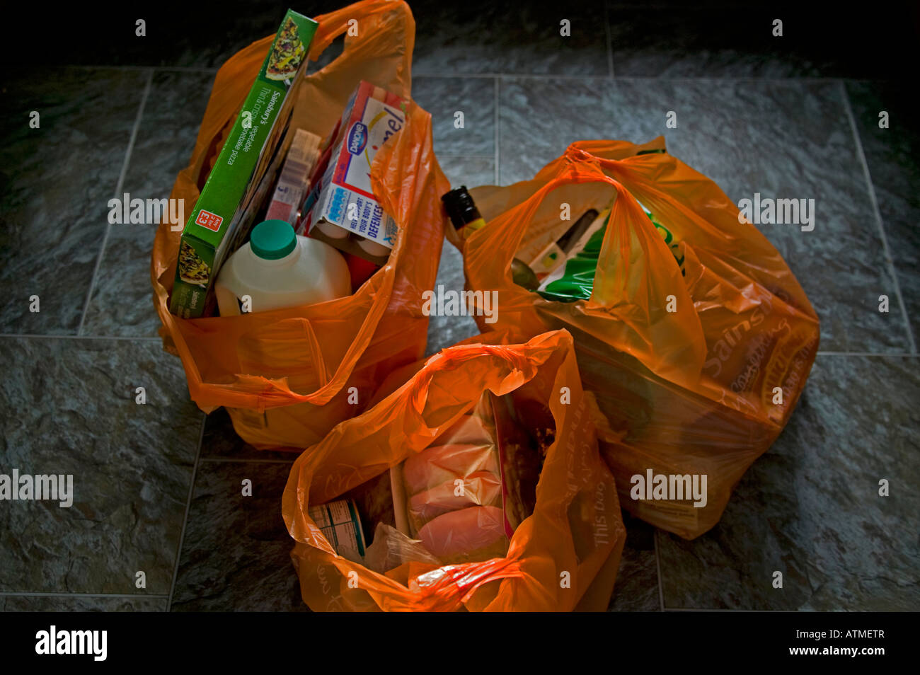 Orange plastic bags filled with shopping, an estimated 1.5bn bags have been used since UK government began phase - Stock Image