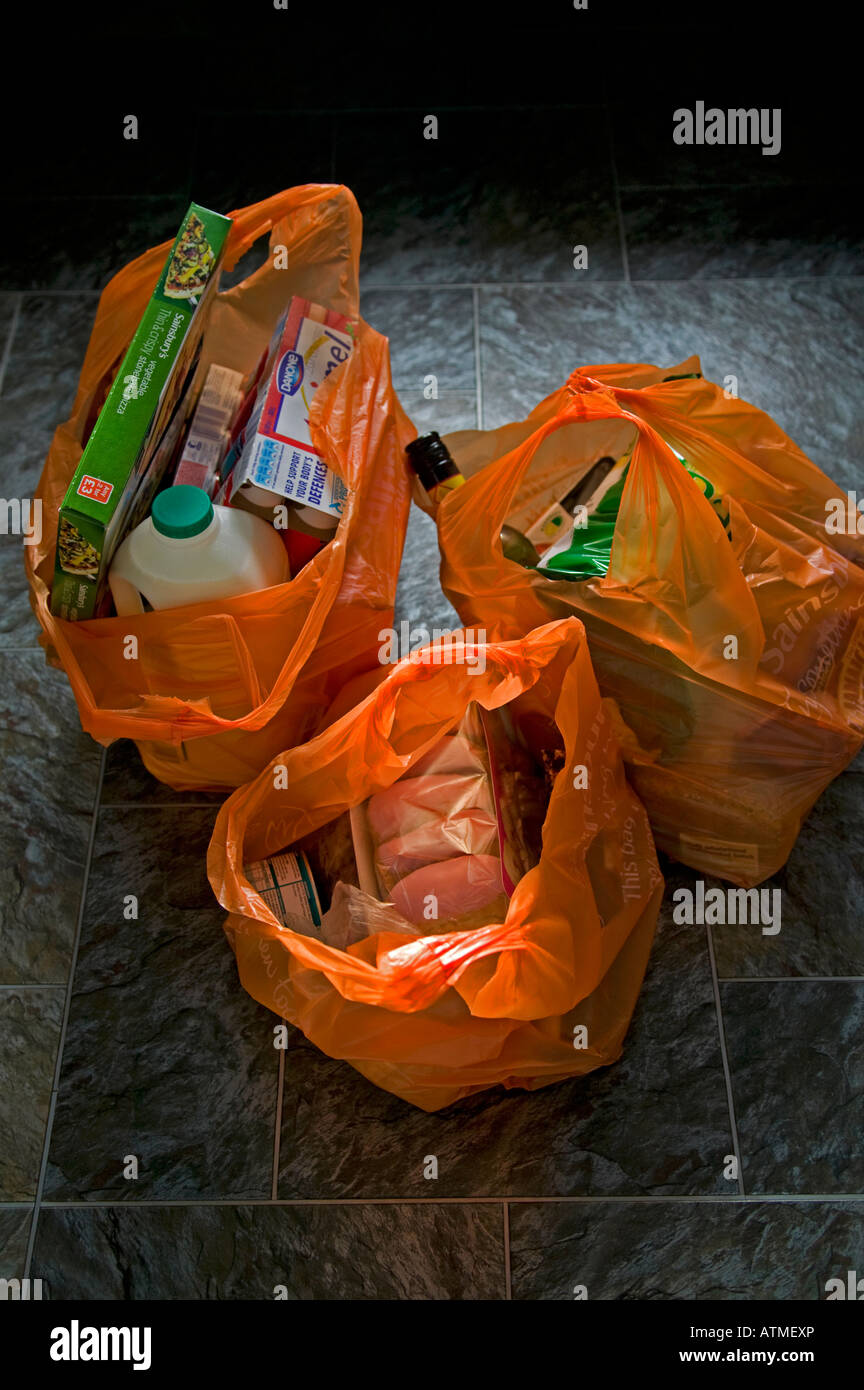 Orange Plastic bags filled with shopping on a tiled floor Scotland, UK - Stock Image