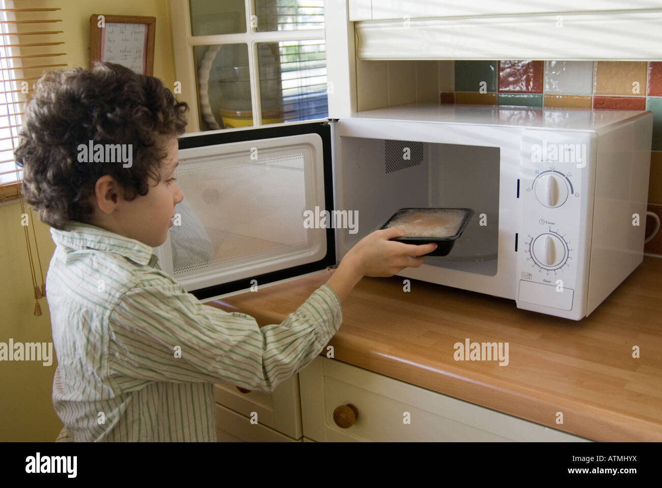 Young child putting ready meal into a microwave oven, England, UK - Stock Image
