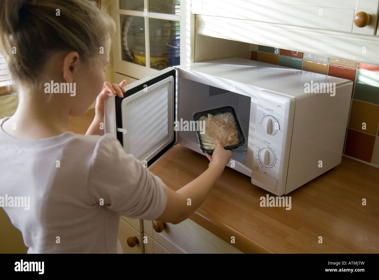 Girl putting ready meal into a microwave oven, England UK - Stock Image