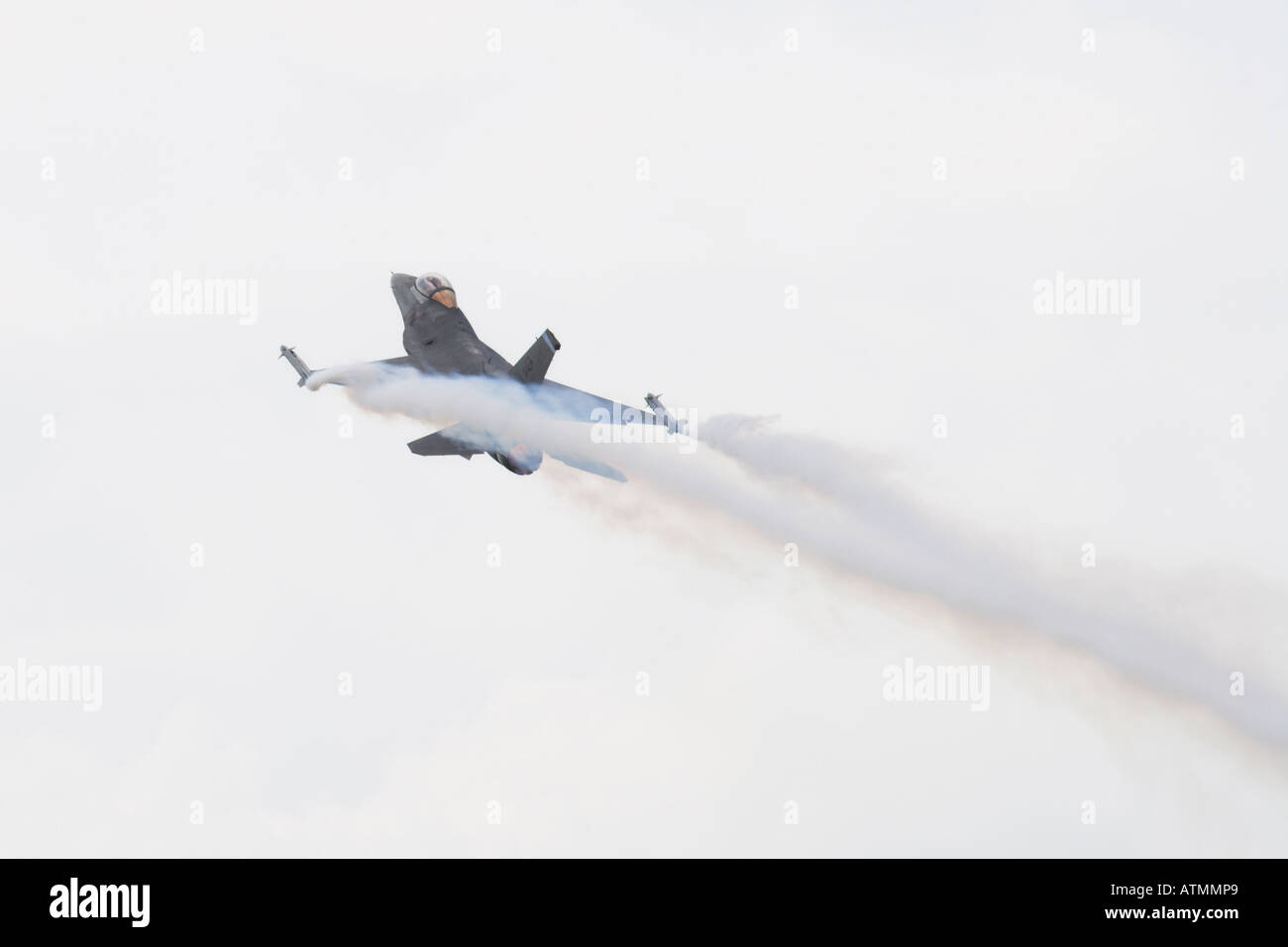 F16 Fighting Falcon taking off with afterburn trailing white marker smoke - Stock Image