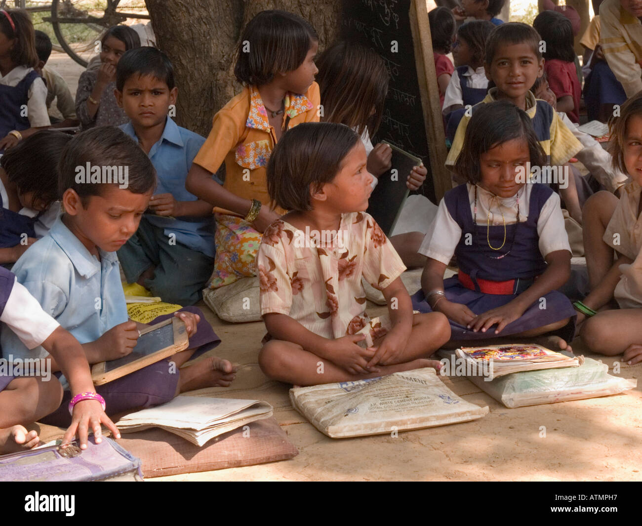 Junior school children sitting on ground with books in shade in rural village for outdoor lesson. Sania Madhya Pradesh India - Stock Image
