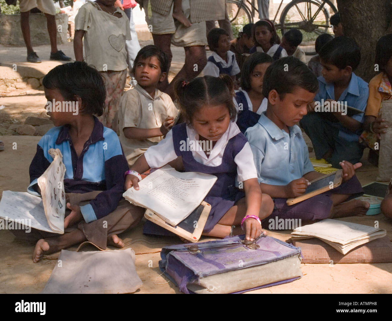 Junior school children sitting on ground with books in shade in rural village for lesson out of doors Sania Madhya Pradesh India - Stock Image