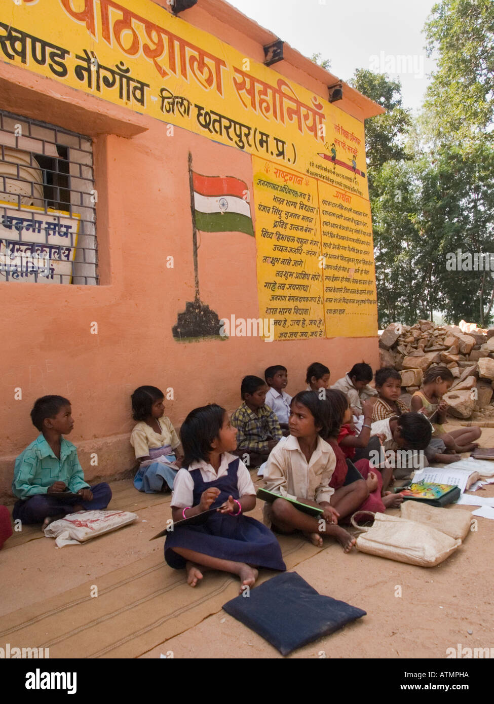 Rows of junior school children sitting on ground in shade outside rural village school for an outdoor lesson. Pradesh India - Stock Image