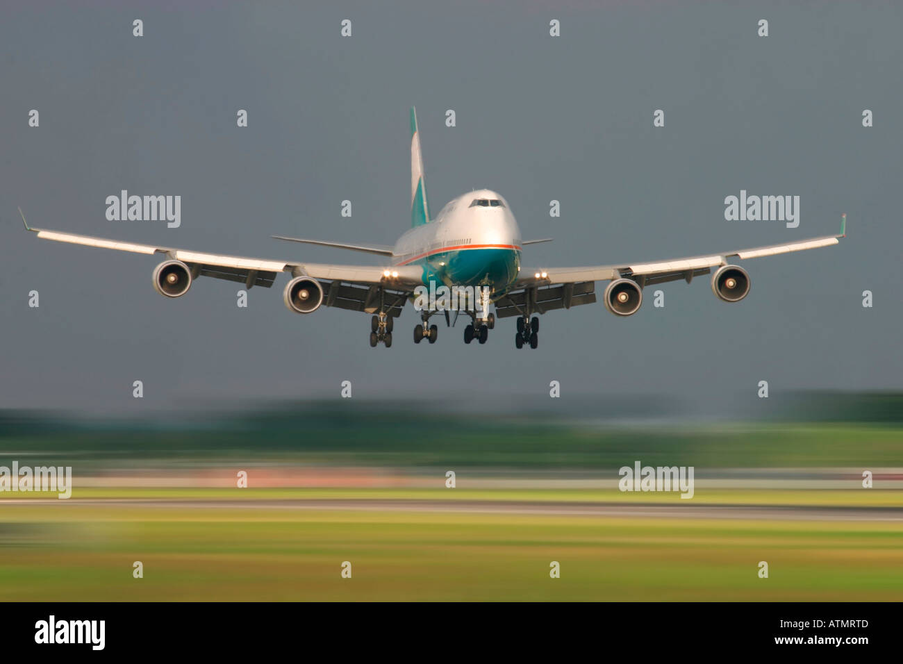 Large passenger jet landing with motion blur in the background - Stock Image