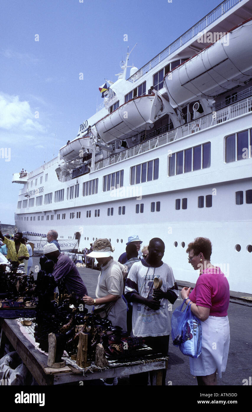 Passengers from an ocean cruise ship bargaining on the dock Zanzibar Tanzania East Africa - Stock Image
