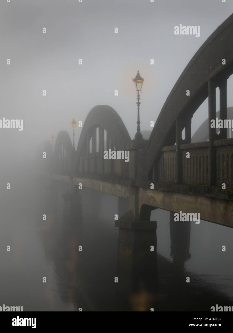 lamplight on foggy bridge - Stock Image