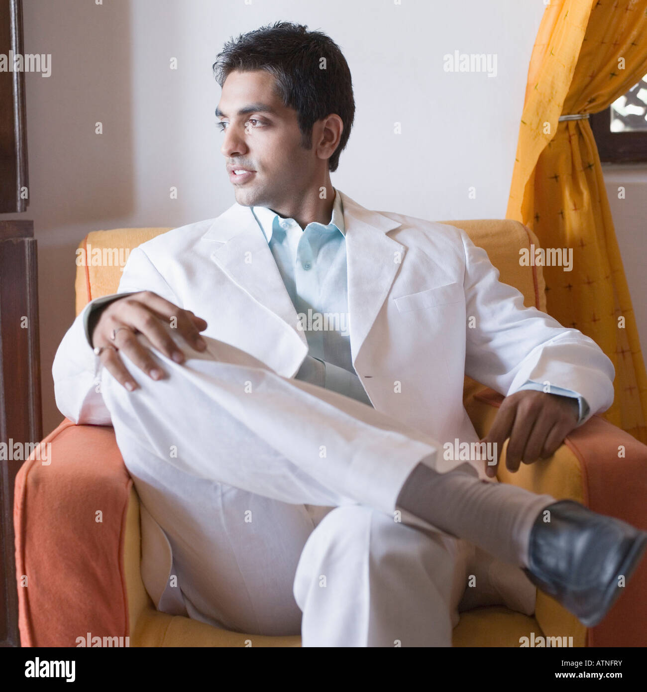 Young man sitting in an armchair with his hand on his knee Stock Photo