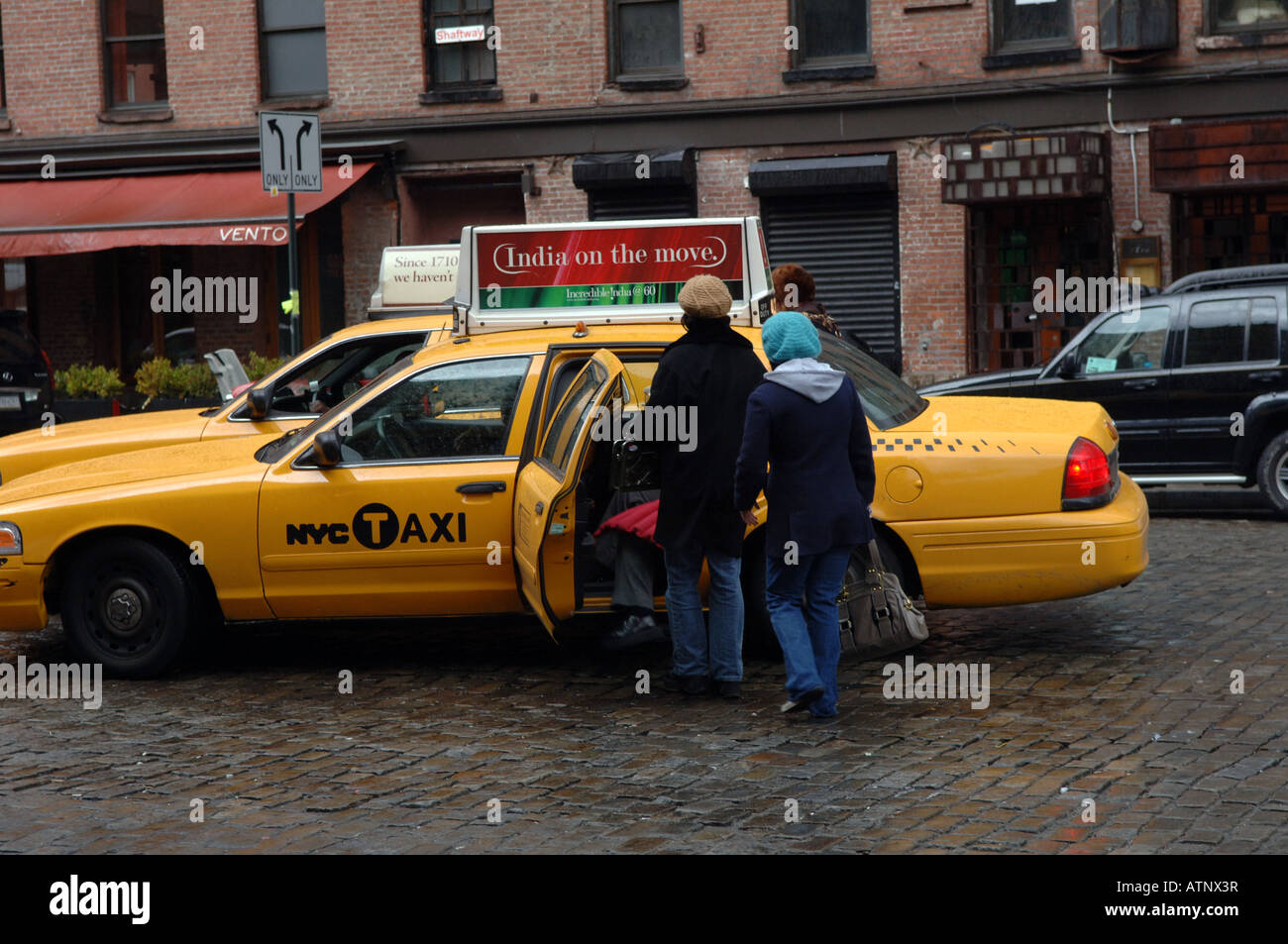 A group of visitors boards a NYC taxicab in the trendy Meatpacking District - Stock Image