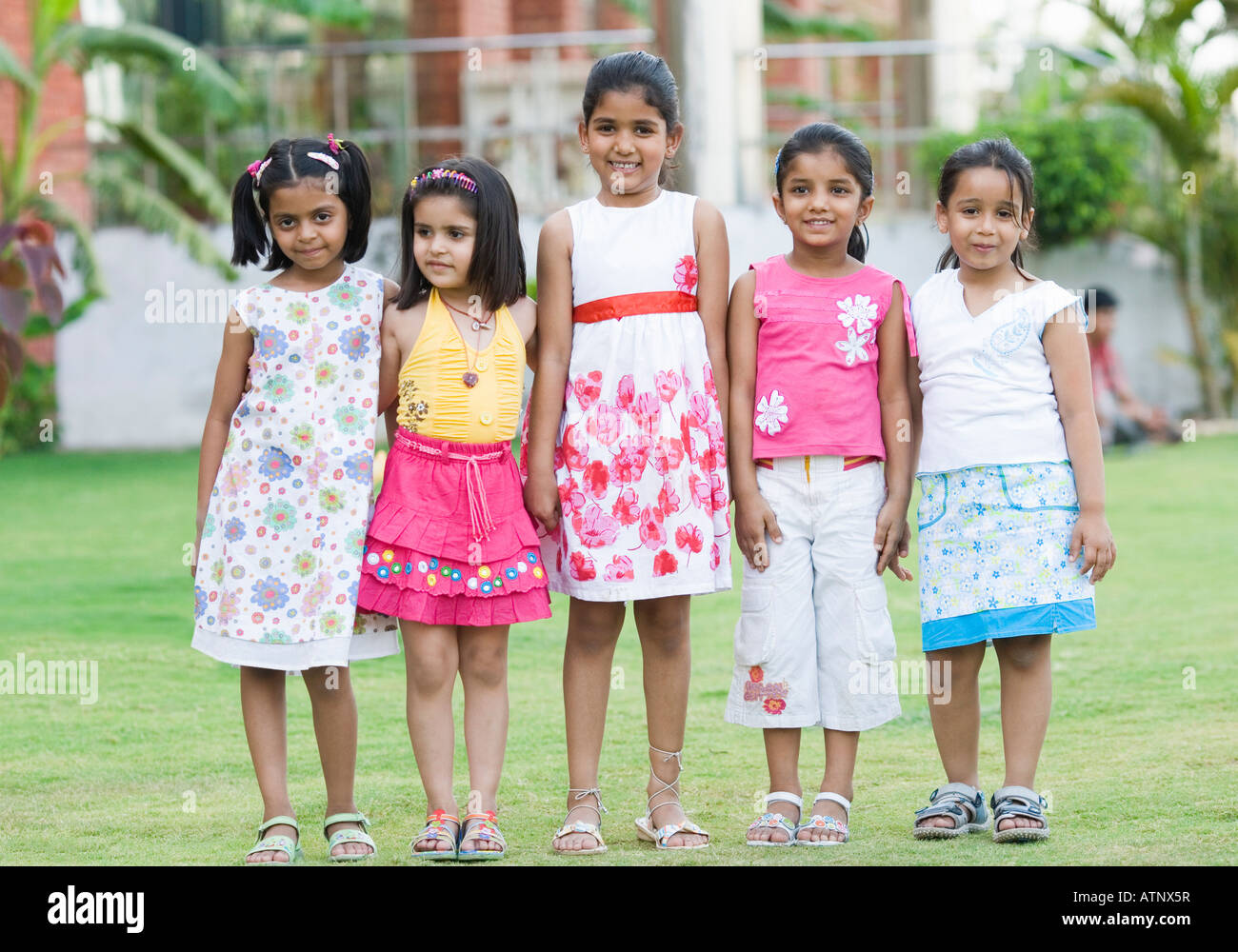 Five girls standing in a lawn and smiling - Stock Image