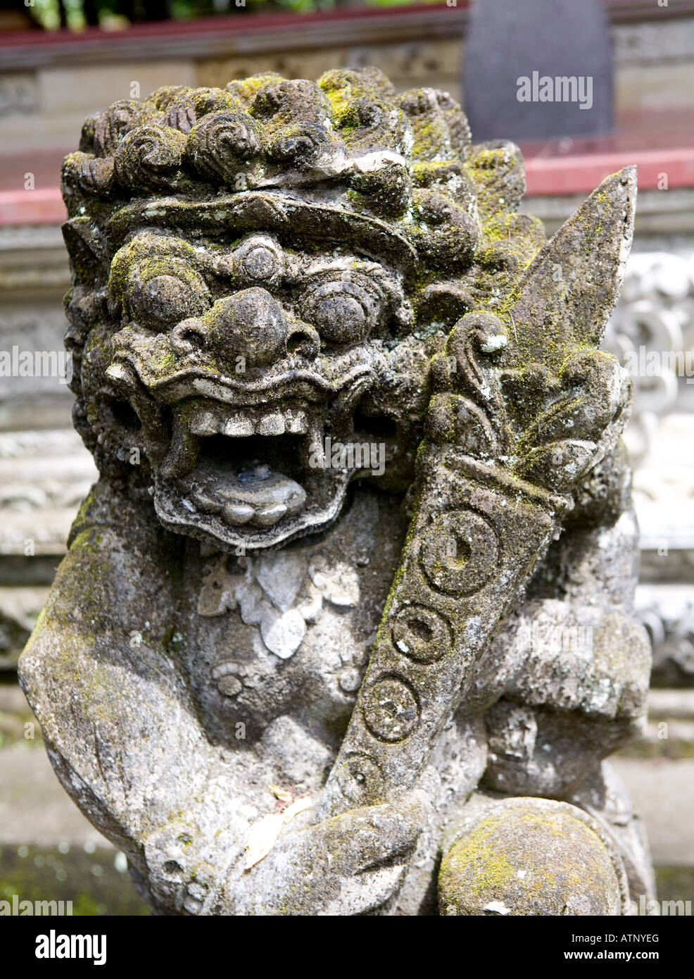 Decorated Animalistic Temple Carving With A Green Mould Face Ubud Bali Indonesia - Stock Image