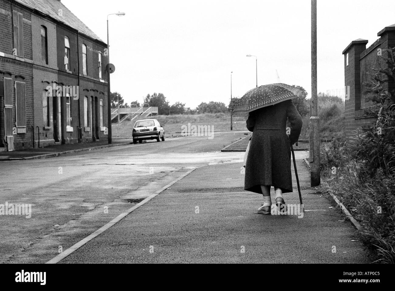Elderly woman walking in rain in urban enviroment - Stock Image