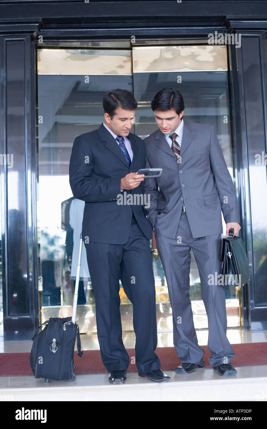 Two businessmen standing in front of the door of a hotel and looking at a mobile phone - Stock Image