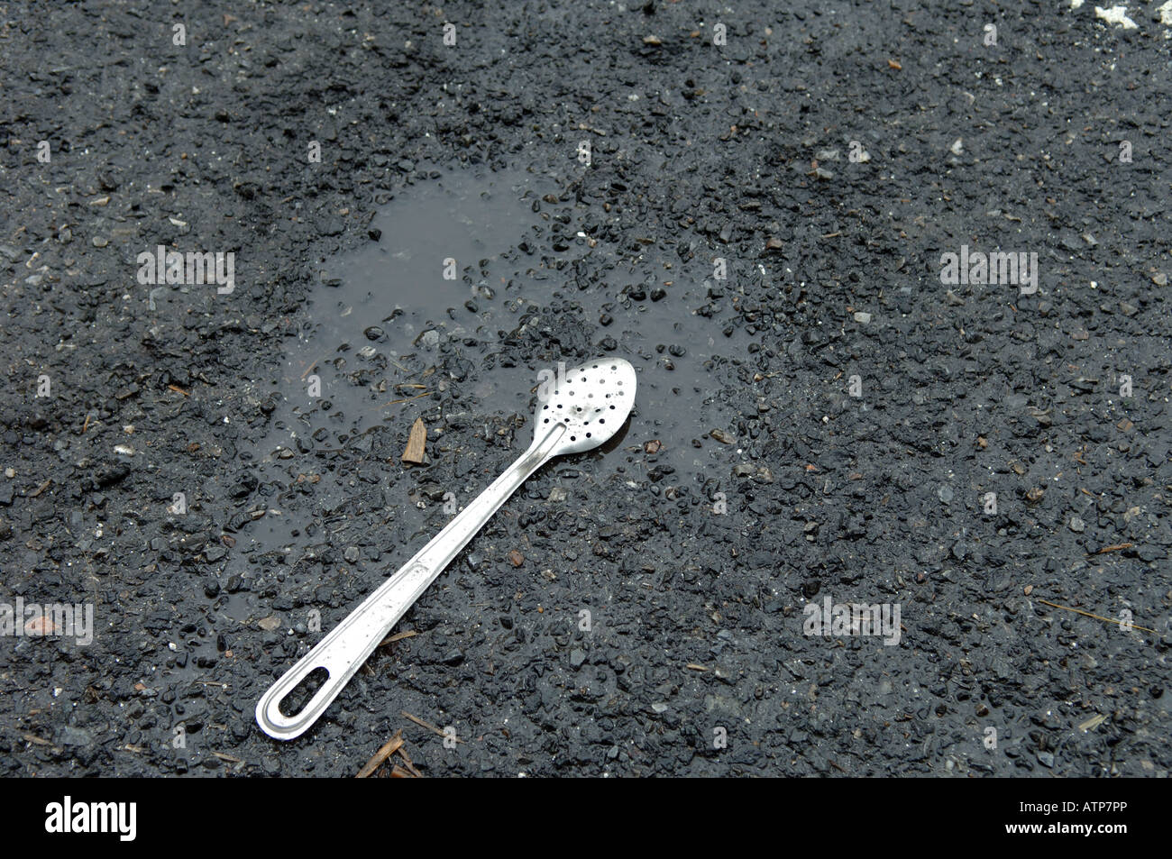 A flattened spoon in the roadway on the Bowery in NYC home of many restaurant suppliers - Stock Image