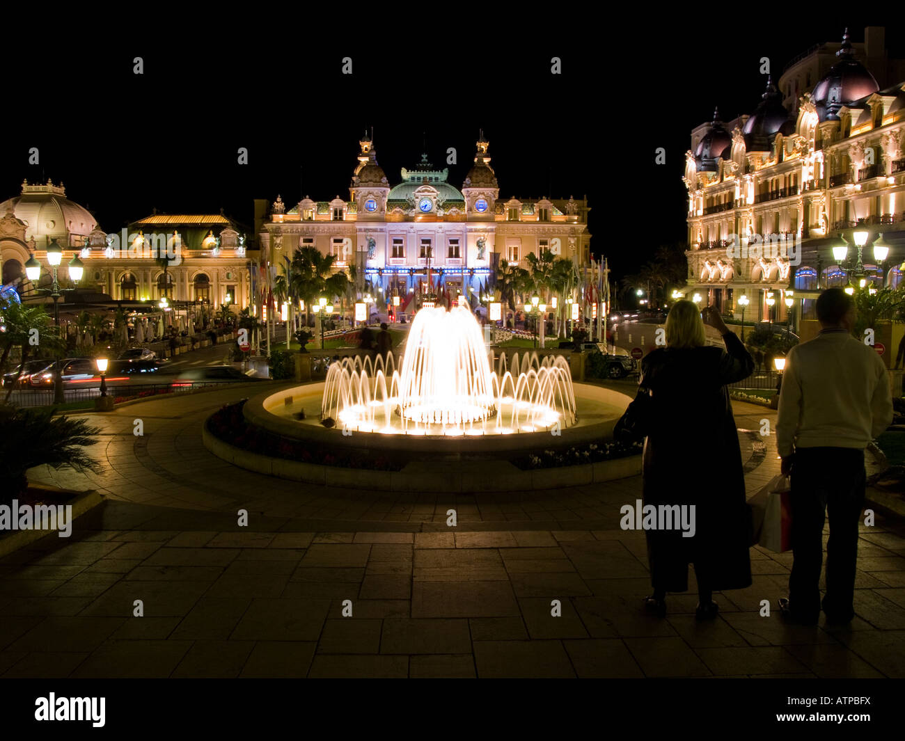 Two tourists and the world-famous Monte Carlo Casino at night in Monaco. Stock Photo