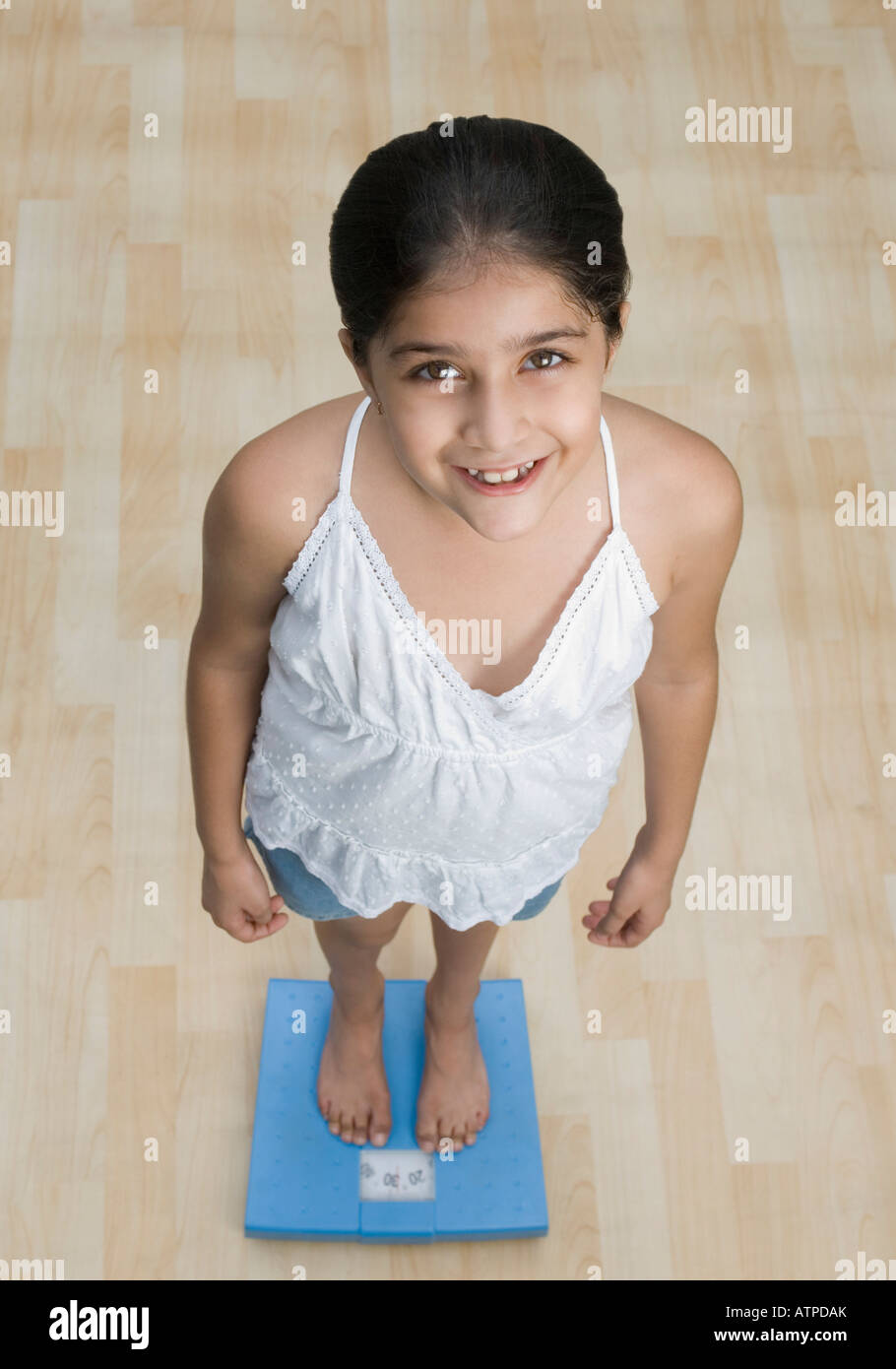 High angle view of a girl standing on a weighing scale and smiling - Stock Image