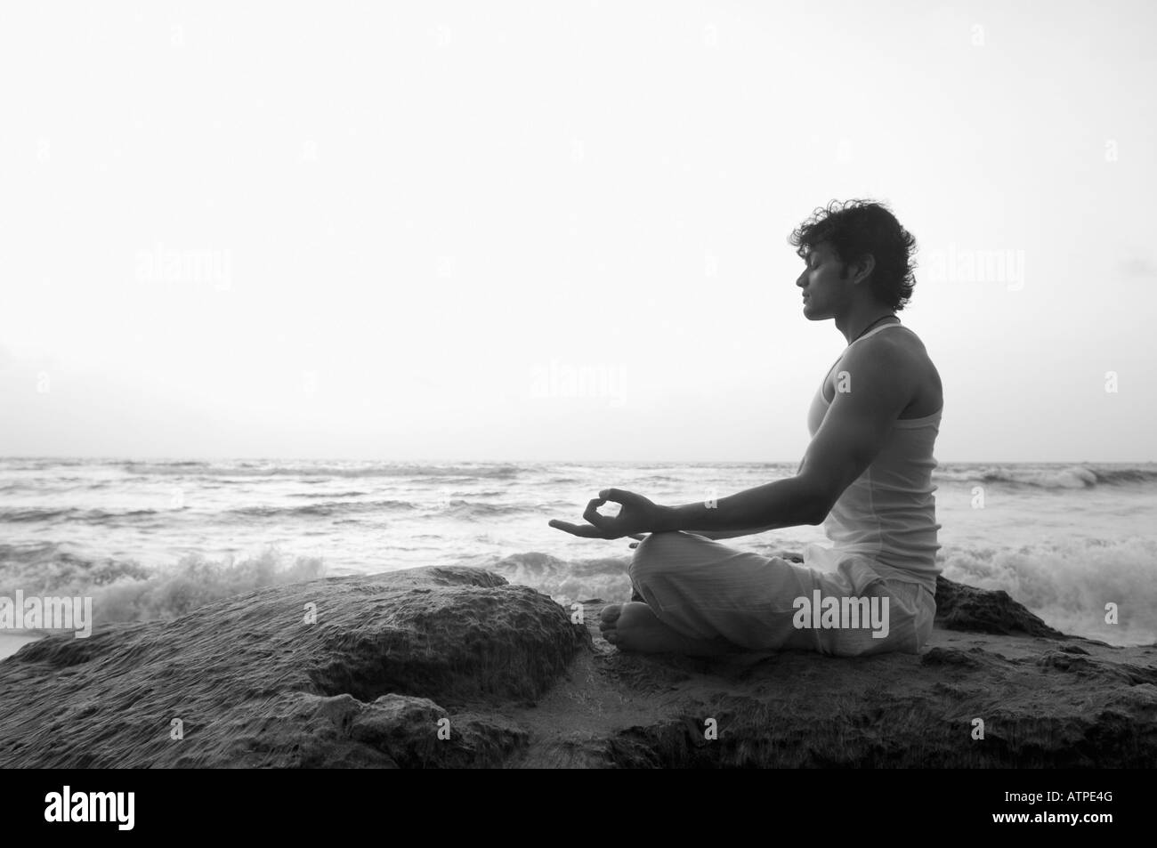 Side profile of a young man meditating on the beach - Stock Image
