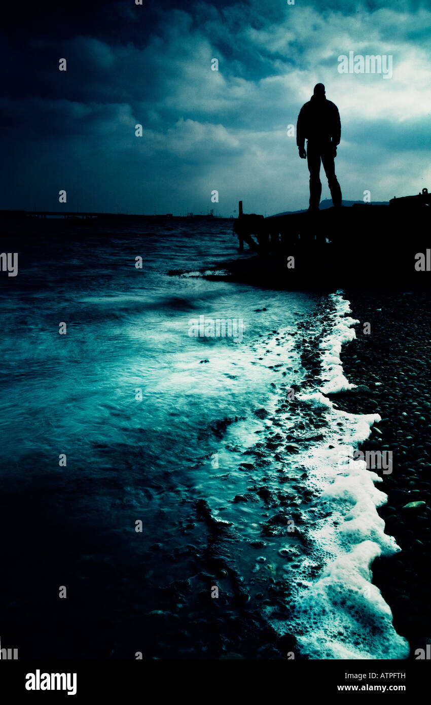 Dark figure standing on jetty looking out to sea - Stock Image