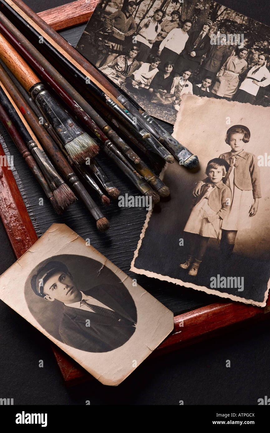 still life of old photographs and used painter's brushes - Stock Image