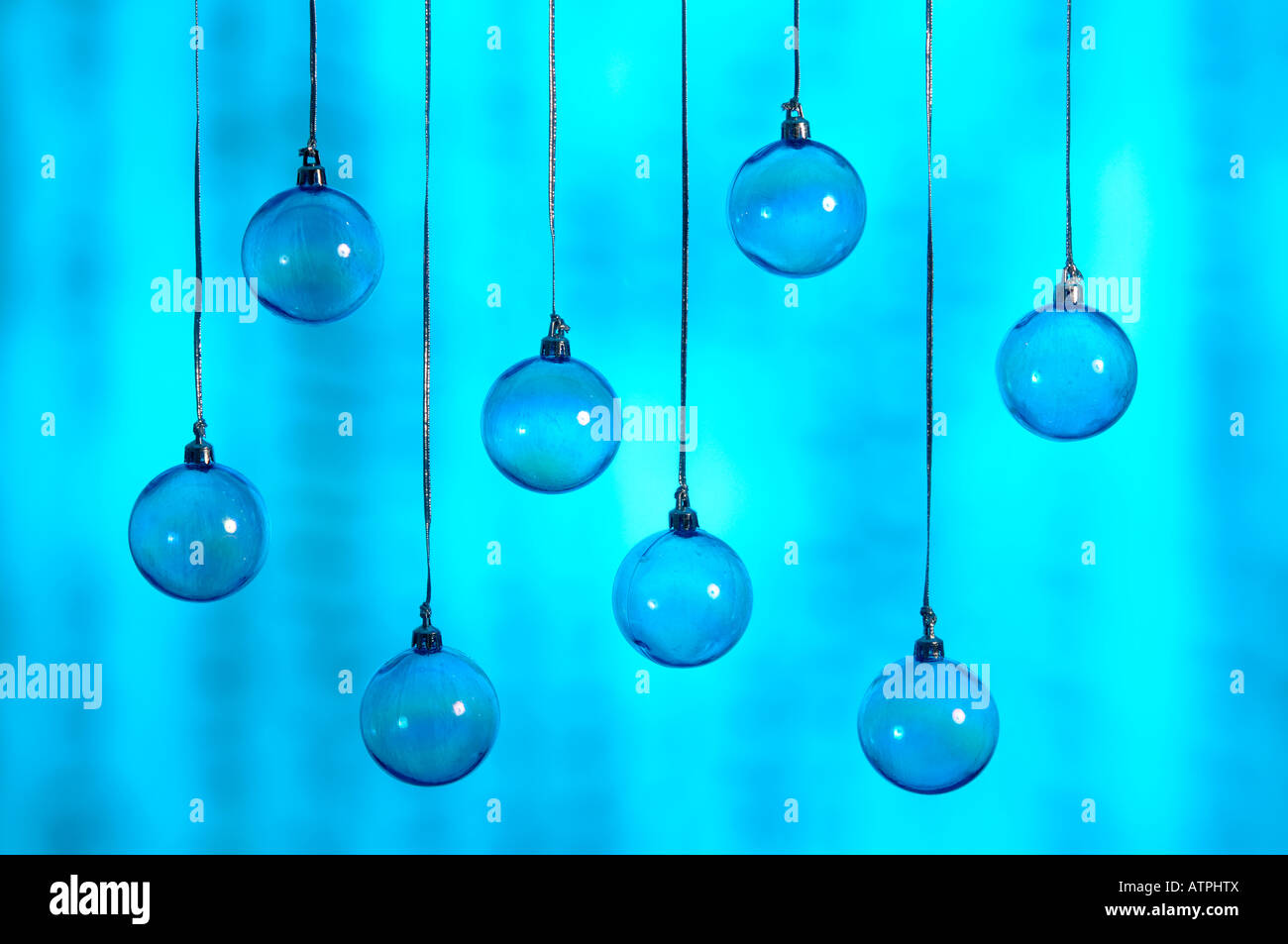 8 blue christmas baubles hanging on silver thread - Stock Image