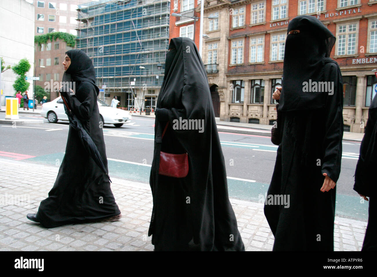 three women walking on a london street on a shopping trip dressed in black in the burka one carrying a handbag - Stock Image