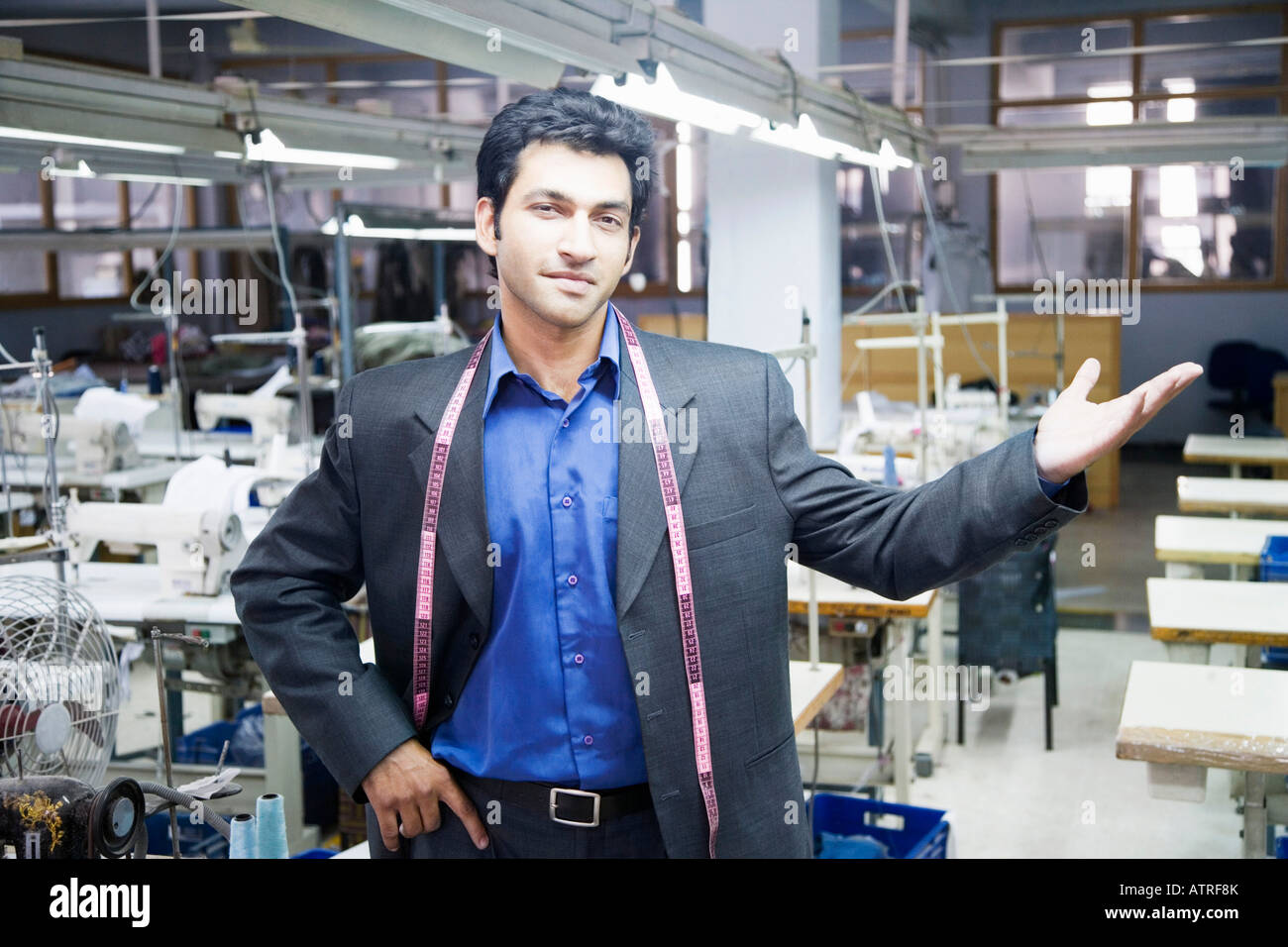 Portrait of a male fashion designer standing in a textile industry - Stock Image
