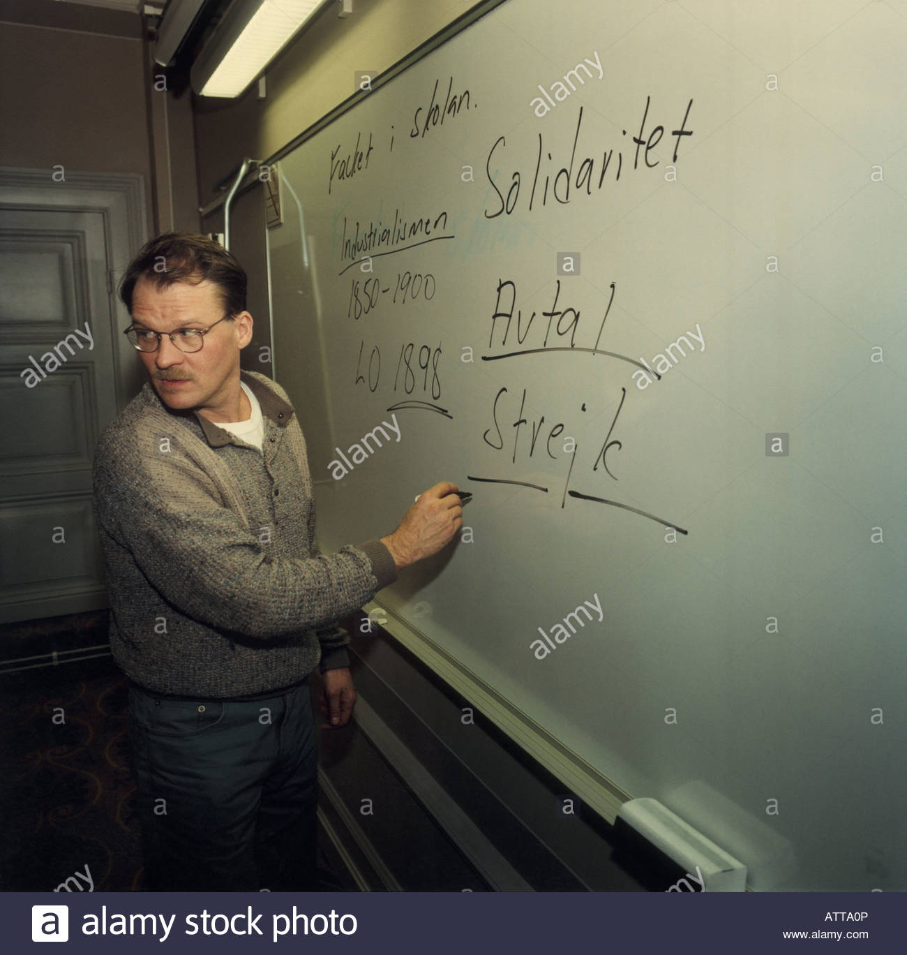Side view of a man turning back while writting on whiteboard - Stock Image