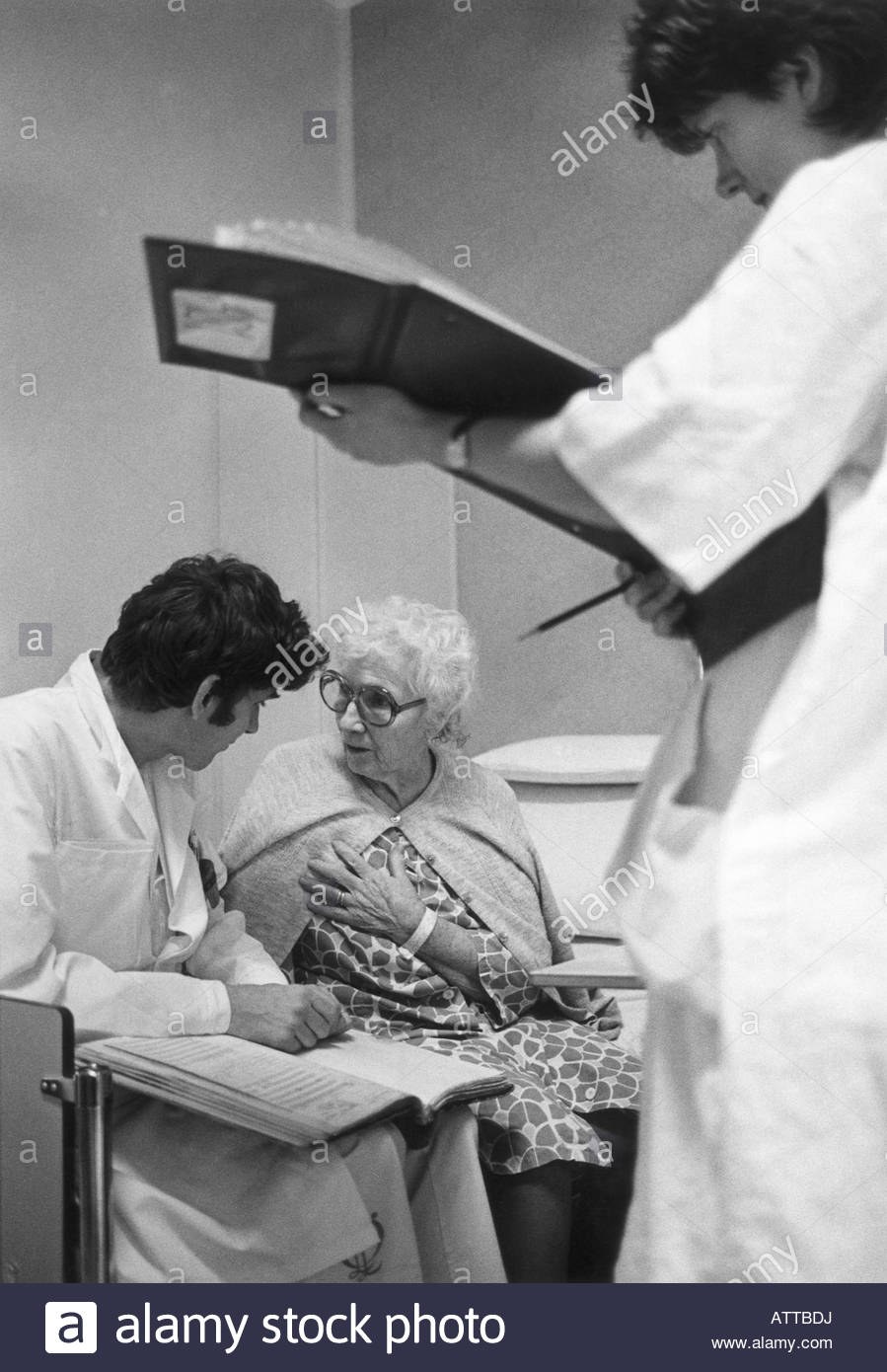 A doctor sitting besides an old woman wearing eyeglasses - Stock Image
