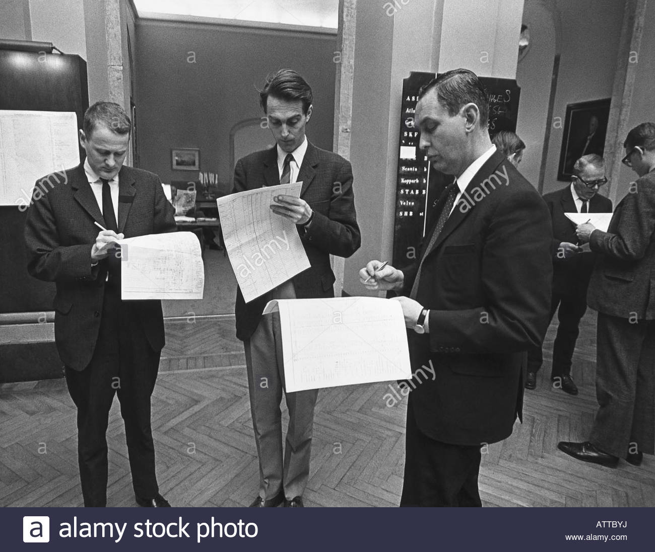 A small group of professionals writting on paper while standing - Stock Image