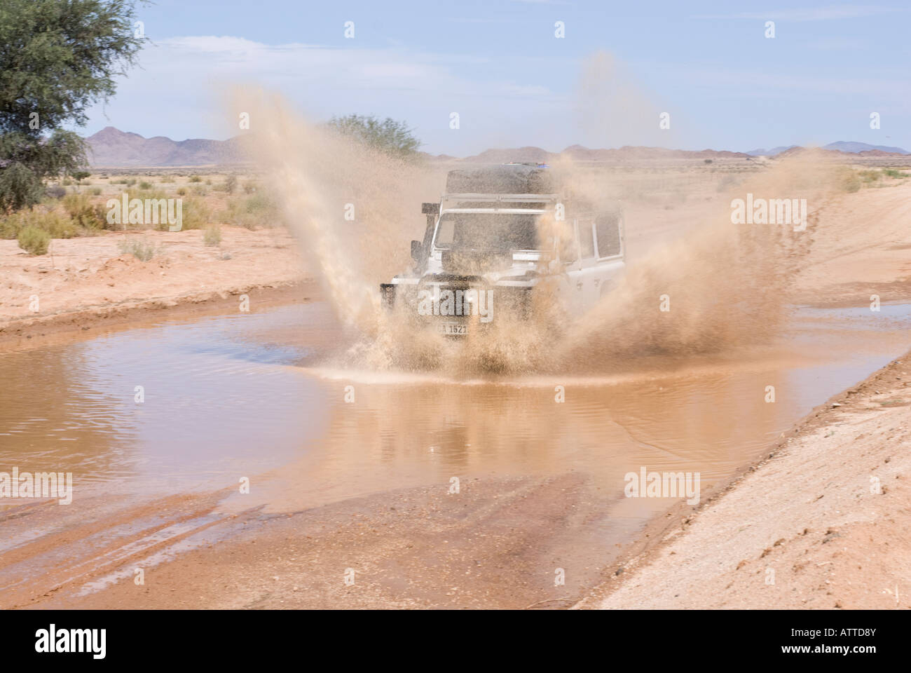 Land Rover blasting through standing water in Namibian desert in Namibia - Stock Image