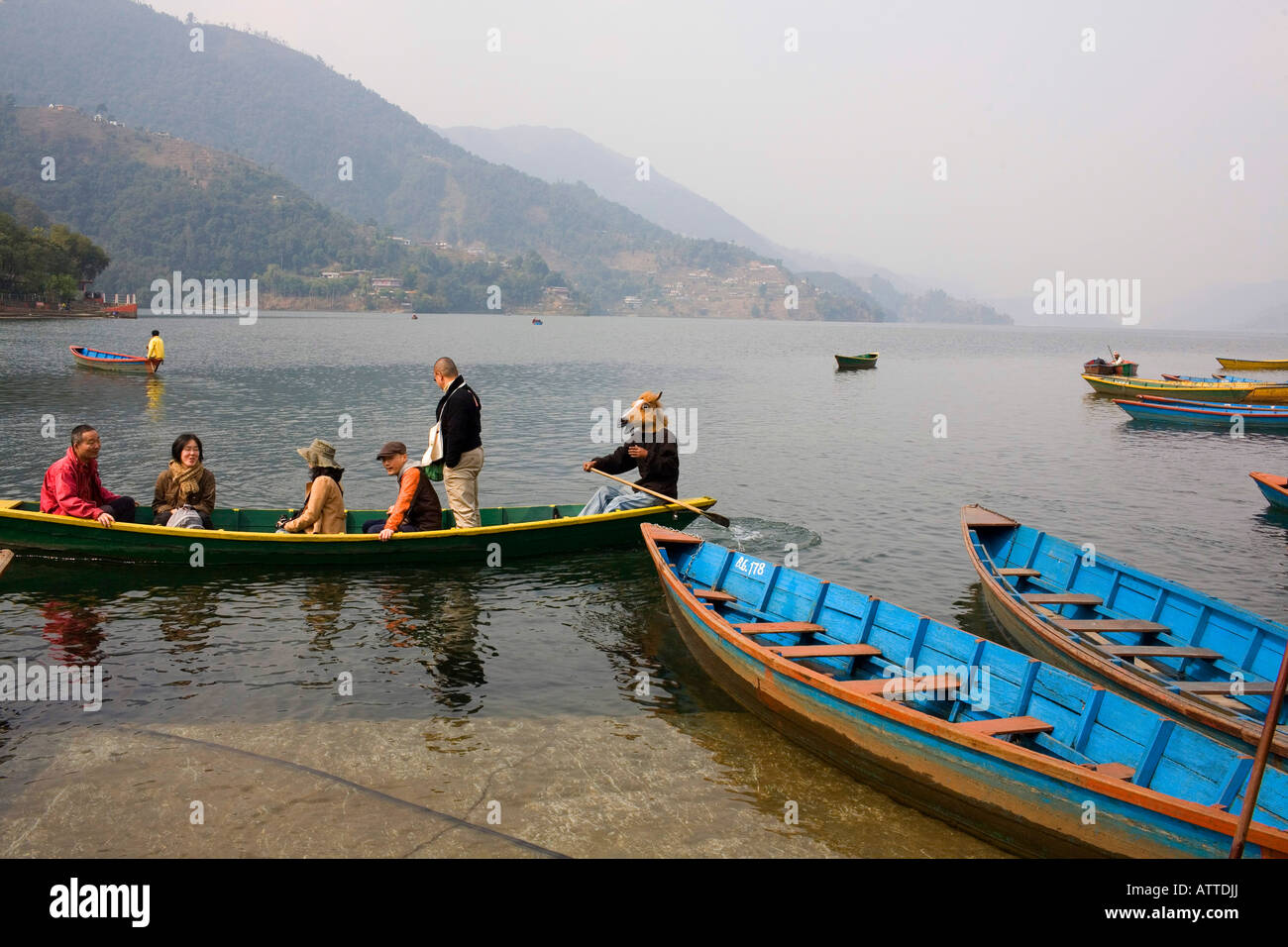 A man in a horse mask ferries tourists across a lake in Pokhara. - Stock Image