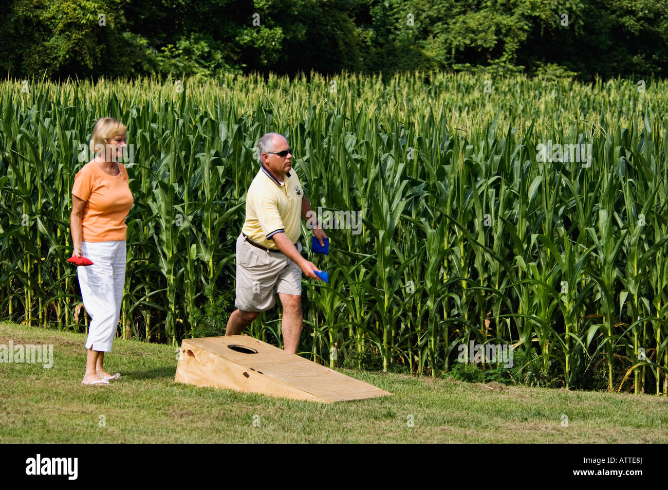 Man and Woman Playing the Game of Cornhole beside Field of Corn Harrison County Indiana - Stock Image