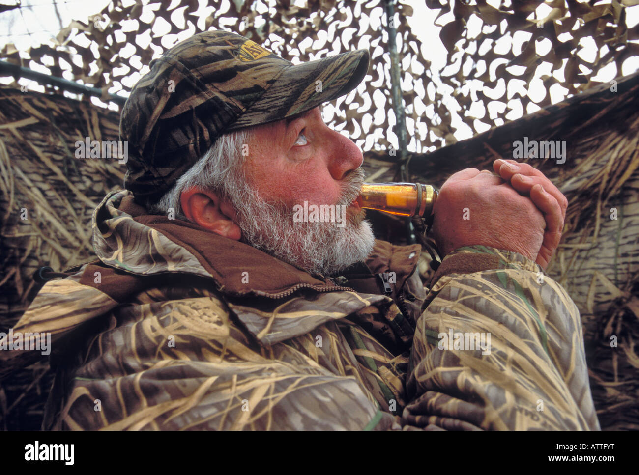 Duck Goose Hunter Calling to Waterfowl as They Fly Past Blind Hardy Lake Southern Indiana - Stock Image