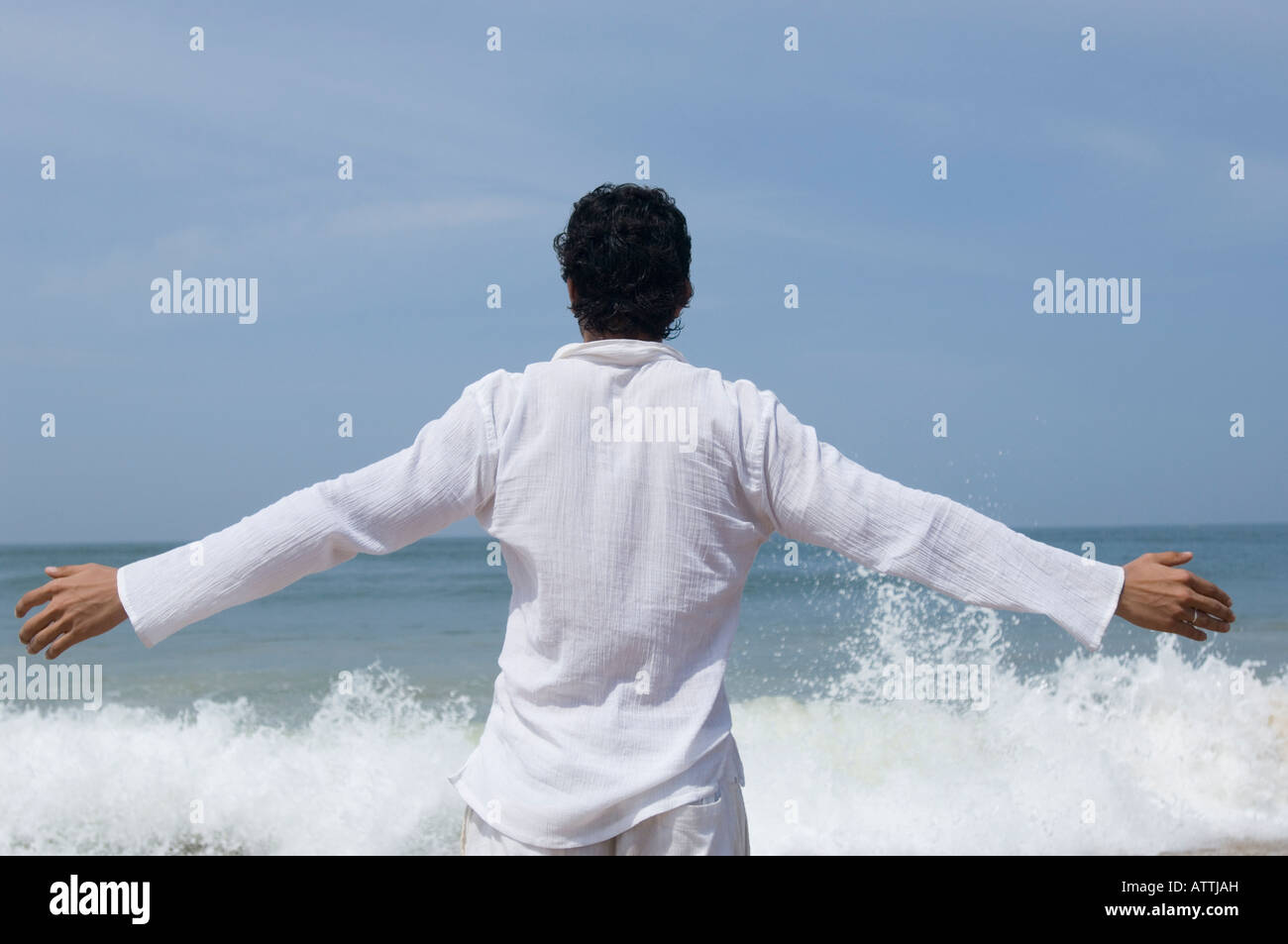 Rear view of a young man standing on the beach Stock Photo