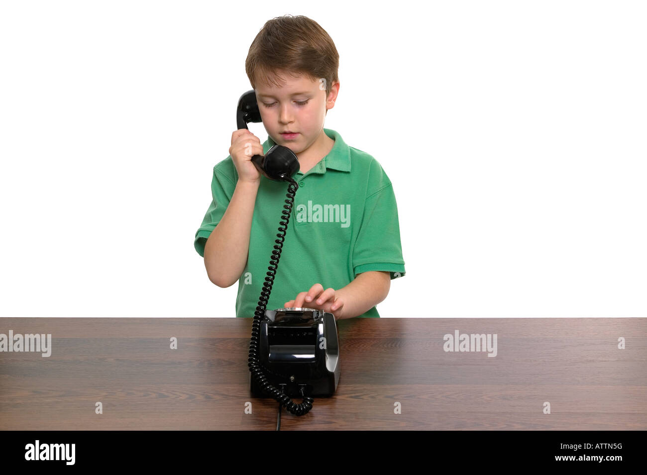 Young boy dialling a number on a retro telephone white background - Stock Image