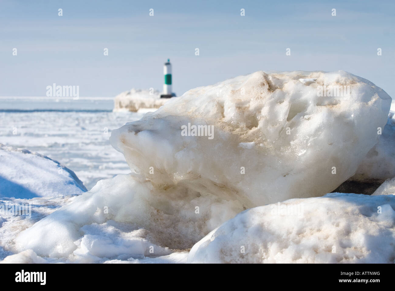 Large chunk of ice and snow with Lake Michigan and a green channel marker light in the background - Stock Image