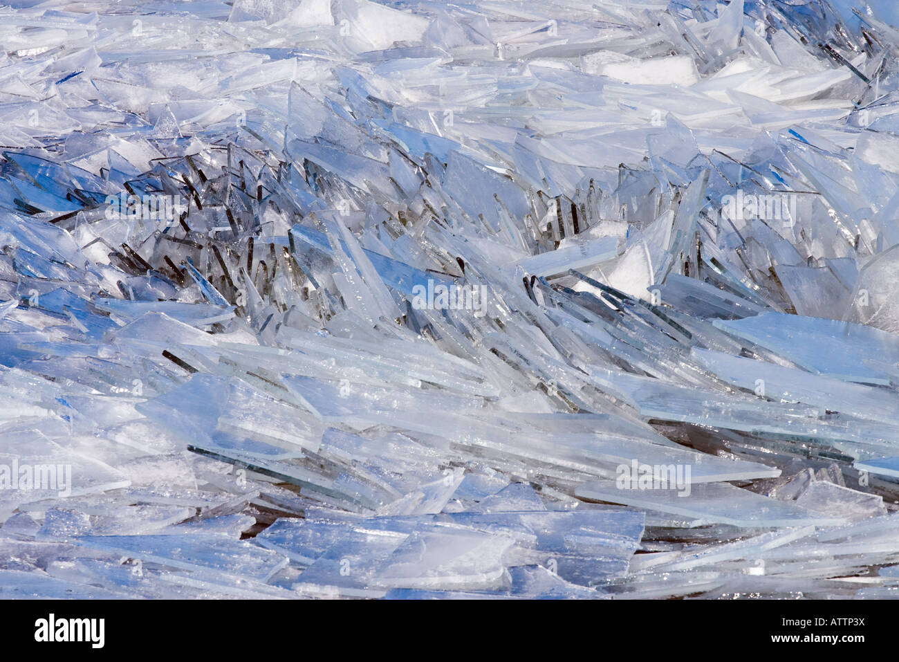 Abstract patterns of broken ice reflecting a cold blue sky in a Lake Michigan Channel - Stock Image