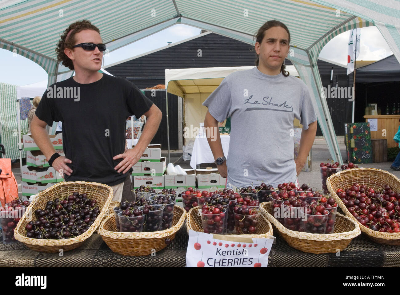 Men selling locally grown Kentish cherries at Farmers Market Whitstable Kent England - Stock Image