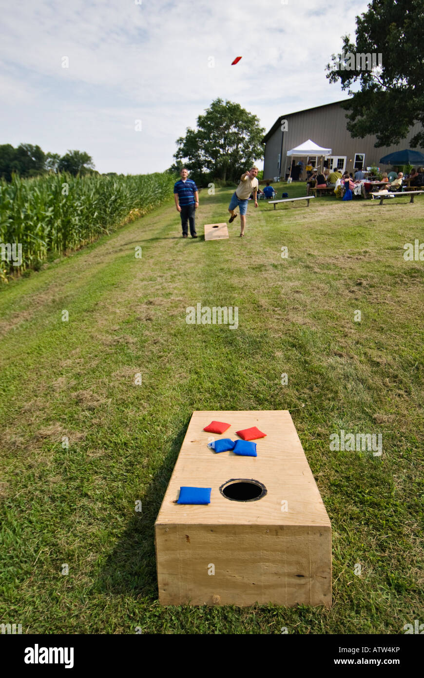 Two Men Playing the Game of Cornhole beside Field of Corn Harrison County Indiana - Stock Image