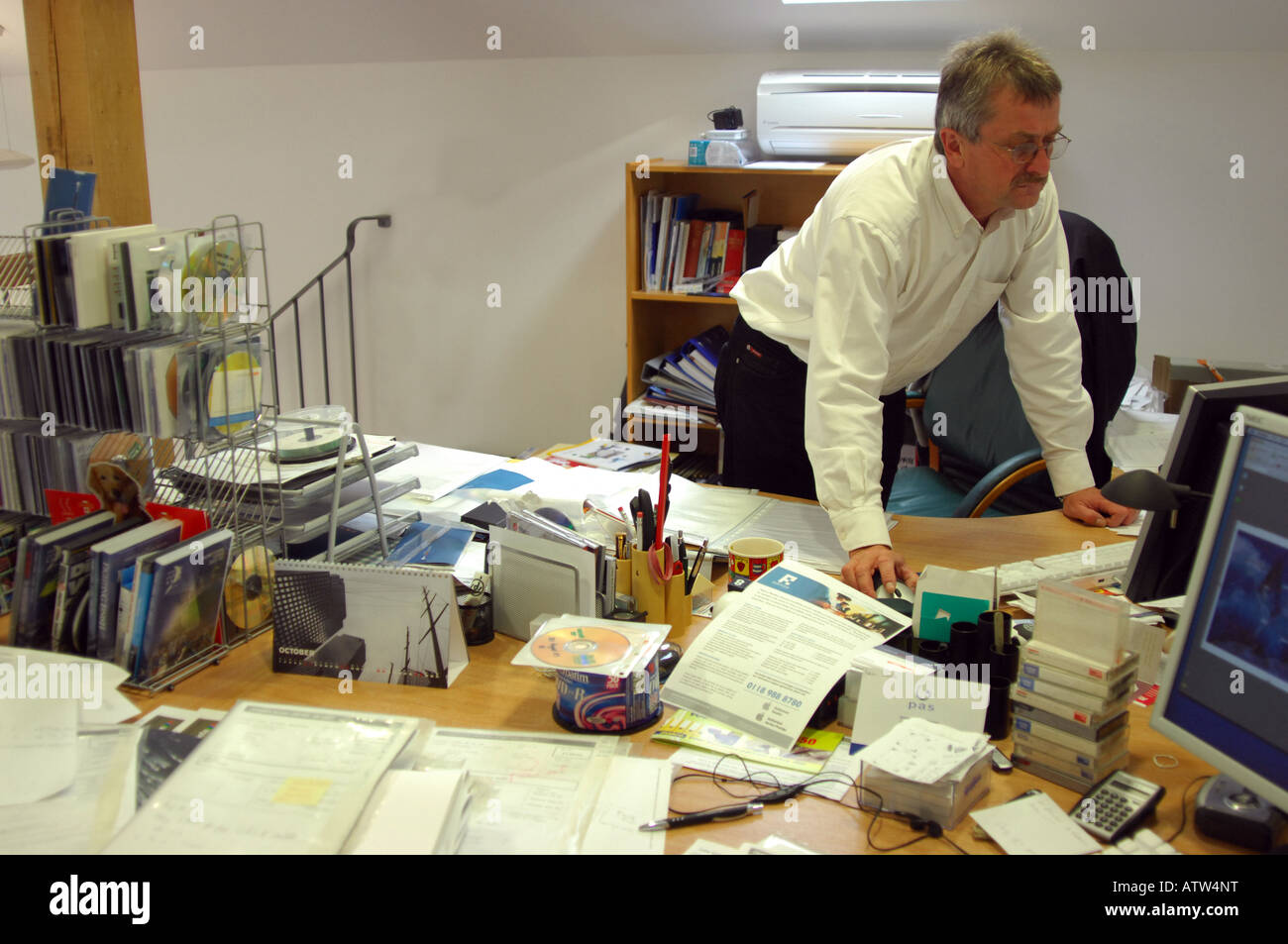 British business man checking emails in messy and untidy hectic corporate offices London UK - Stock Image