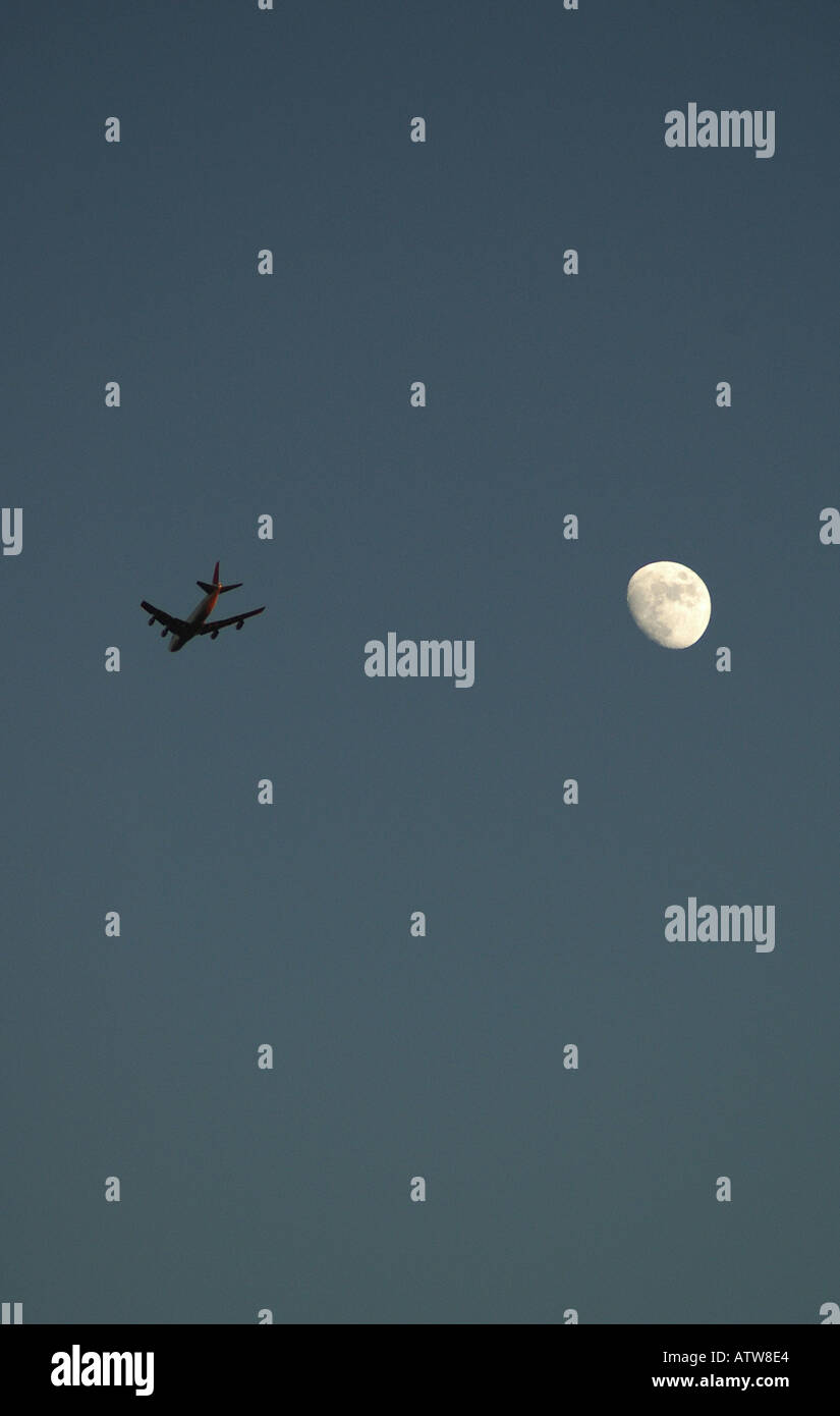 Red Eye Flight Passing The Moon Stock Photo