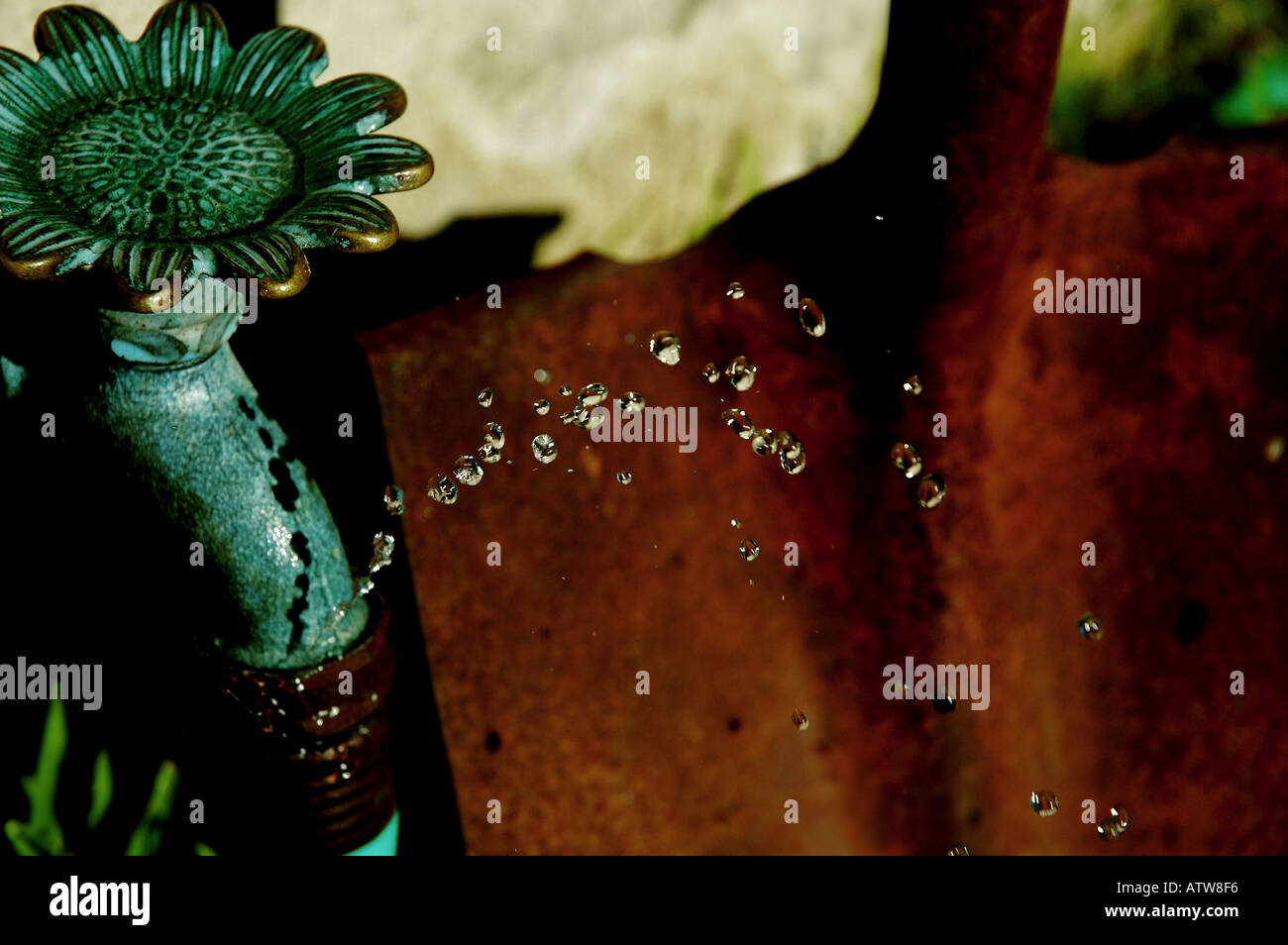 Springs a Leak - Copper Faucet, Hose, & Rusty Shovel Stock Photo