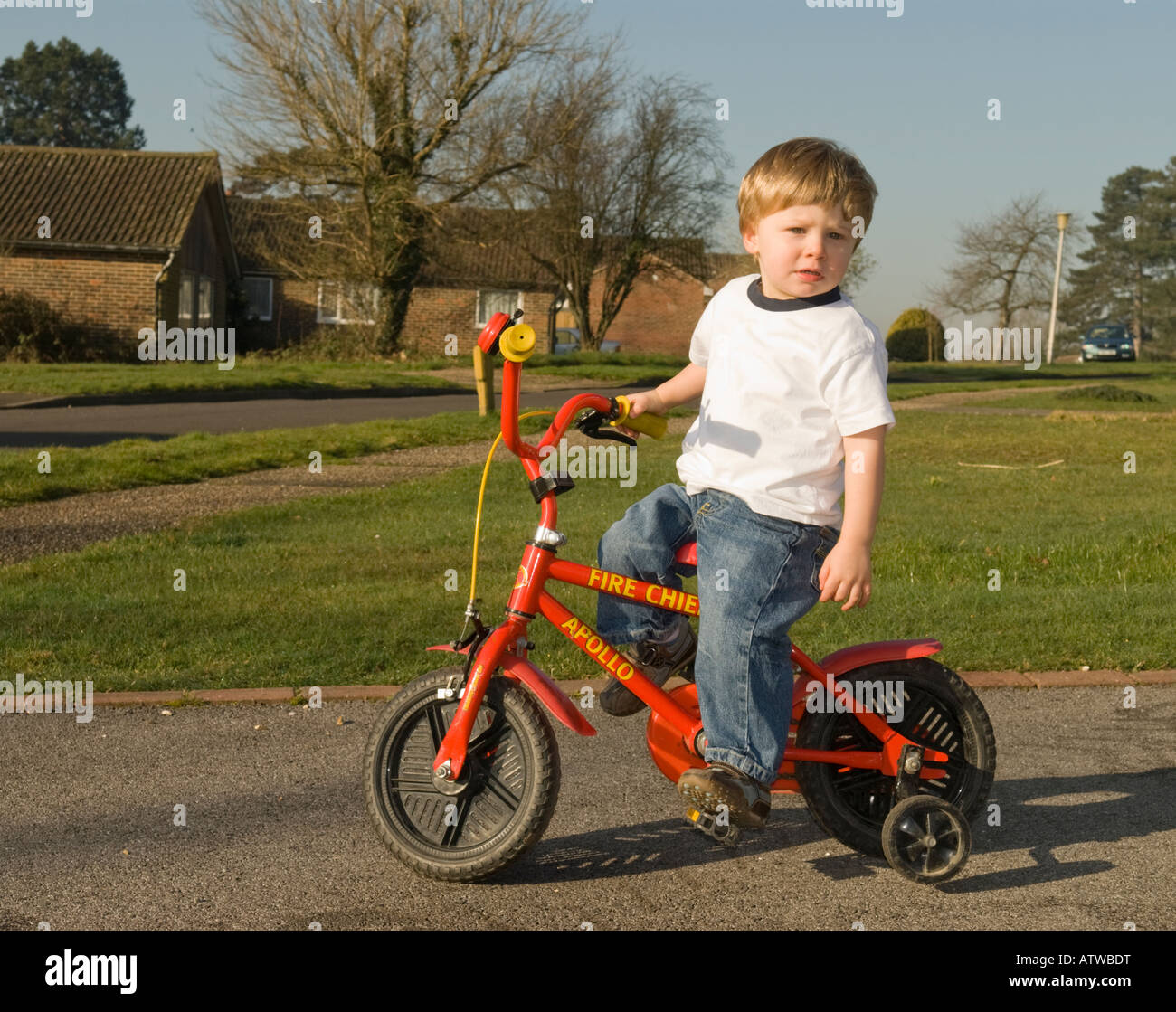 Two Year Old Boy Learning To Ride A Bike Fitted With Stabilizers