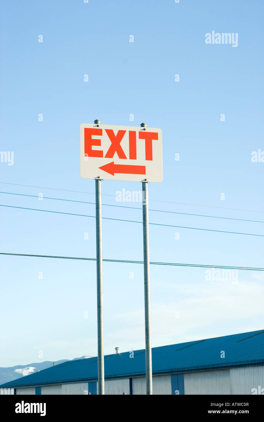Parking lot exit sign with arrow against a blue sky - Stock Image