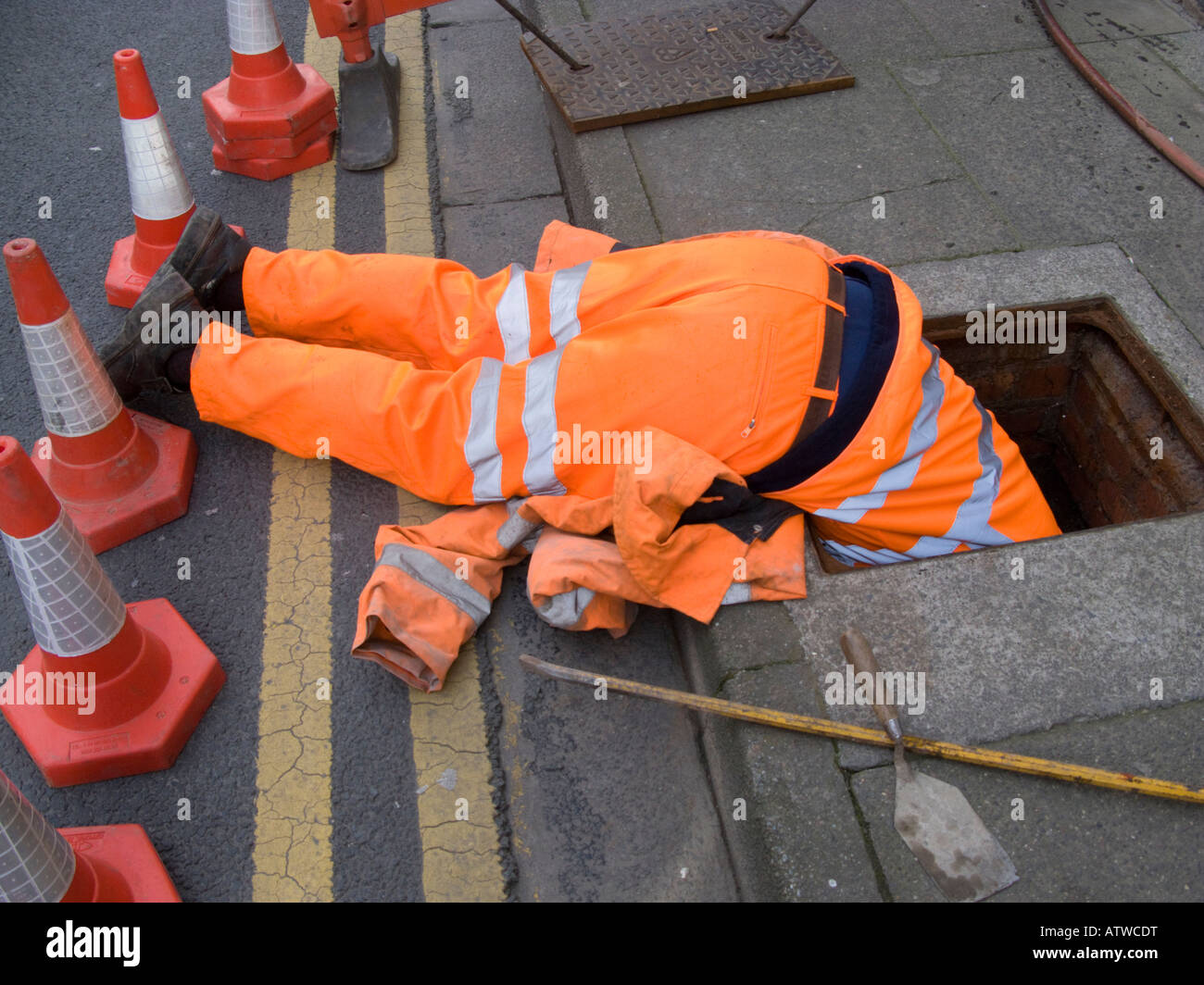 Dyno Rod Worker Wearing Orange Overalls Head First Down A