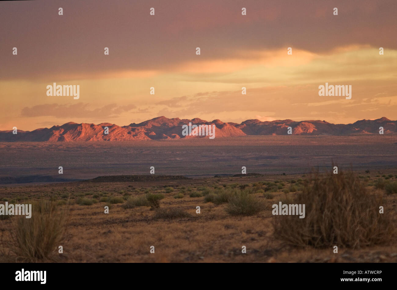 Plains and mountains surrounding the Fish River Canyon in souther Namibia with magenta sunset and rain clouds - Stock Image