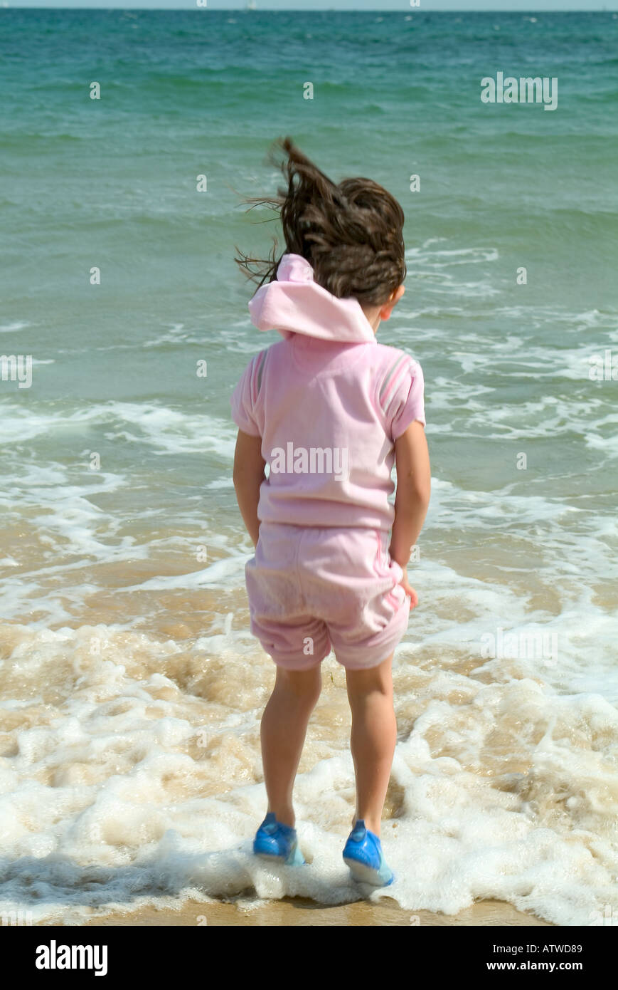 a young girl paddling at the edge of the sea - Stock Image